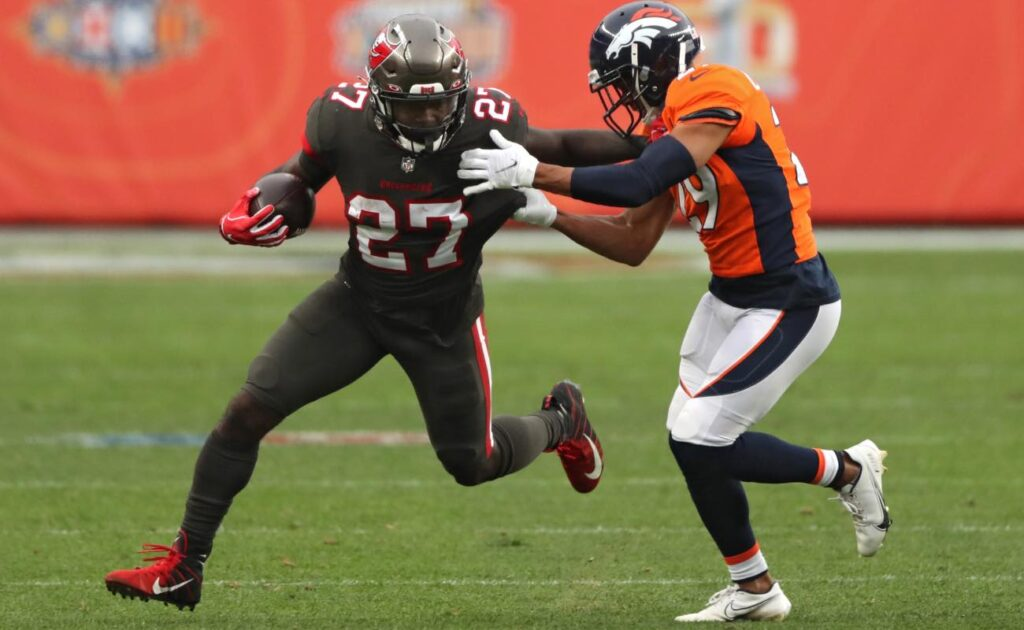 Ronald Jones of Tampa Bay Buccaneers rushes past Bryce Callahan of Denver Broncos at Empower Field September 2020