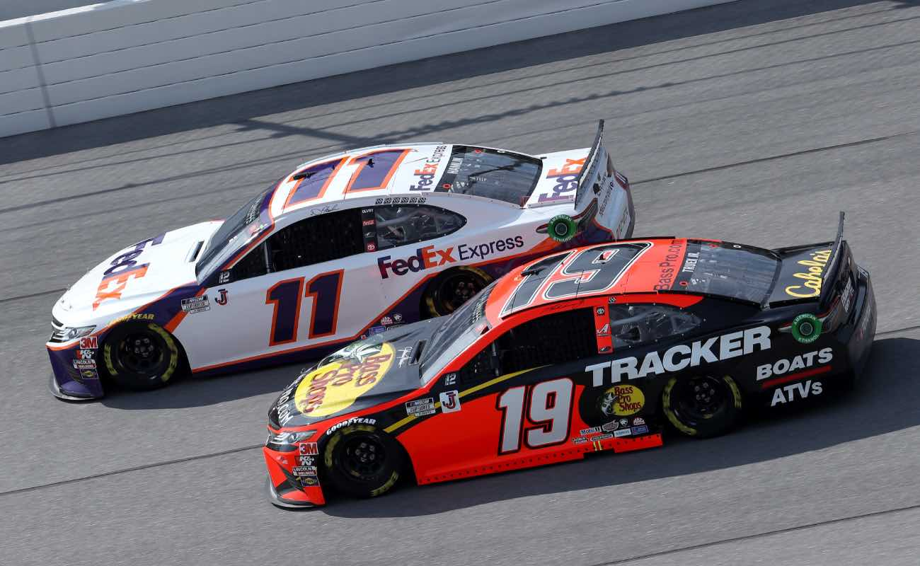 Denny Hamlin, driver of the #11 FedEx Express Toyota, and Martin Truex Jr., driver of the #19 Bass Pro Shops Toyota, race during  NASCAR Cup Series YellaWood 500
