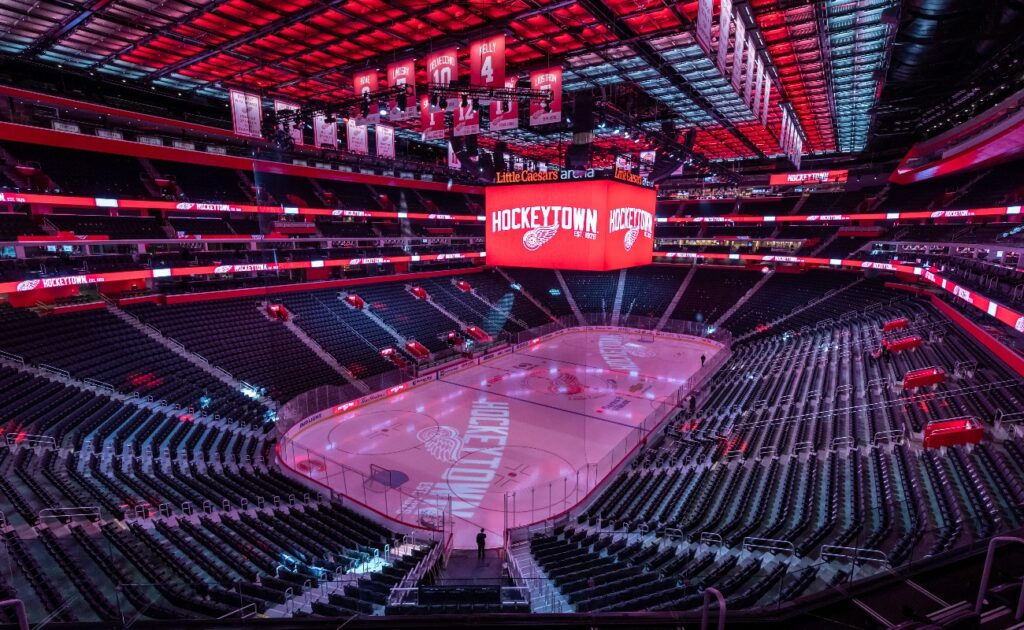 Overview of the empty ice hockey field in the Little Caesars Arena dressed with the Detroit Red Wings colors