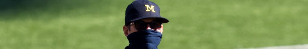 American football coach Jim Harbaugh wearing a black mask, sunglasses and a Michigan Wolverines football team cap