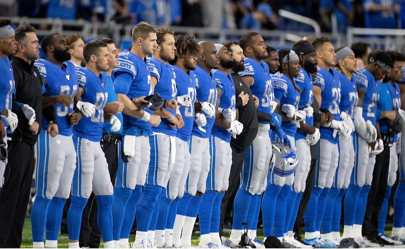 Members of the Detroit Lions line up for the playing of the National Anthem prior to the start of the game against the New York Giants at Ford Field on October 27, 2019 in Detroit, Michigan. Detroit defeated New York 31-26. (Photo by Leon Halip/Getty Images)