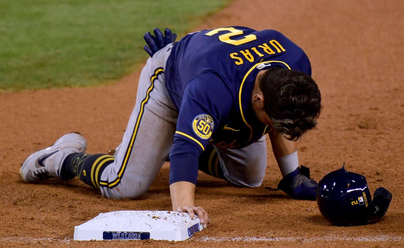 Luis Urias of the Milwaukee Brewers collapses to his knees after he is picked off at first base. Photo by Harry How/Getty Images