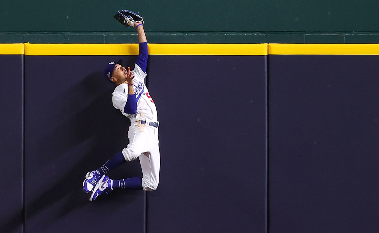 Mookie Betts of the Los Angeles Dodgers slides towards the plate against Dansby Swanson of the Atlanta Braves. Photo by Ron Jenkins/Getty Images