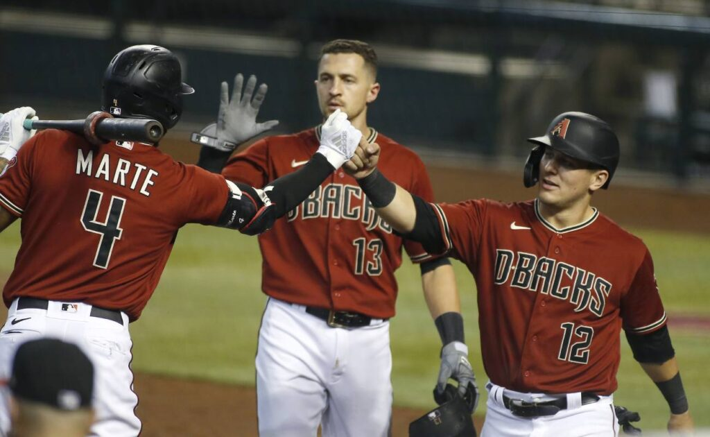 Daulton Varsho 12 and Ketel Marte of the Diamondbacks bump fists. Photo by Ralph Freso/Getty Images