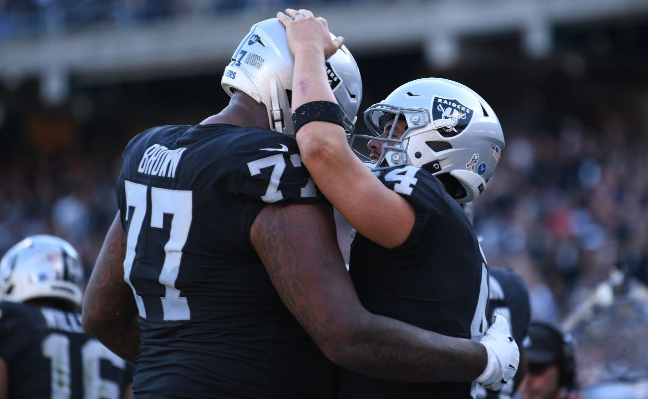 Derek Carr #4 of the Oakland Raiders celebrate with Trent Brown #77 after scoring in the second quarter against the Cincinnati Bengals during their NFL game at RingCentral Coliseum on November 17, 2019 in Oakland, California. (Photo by Robert Reiners/Getty Images)