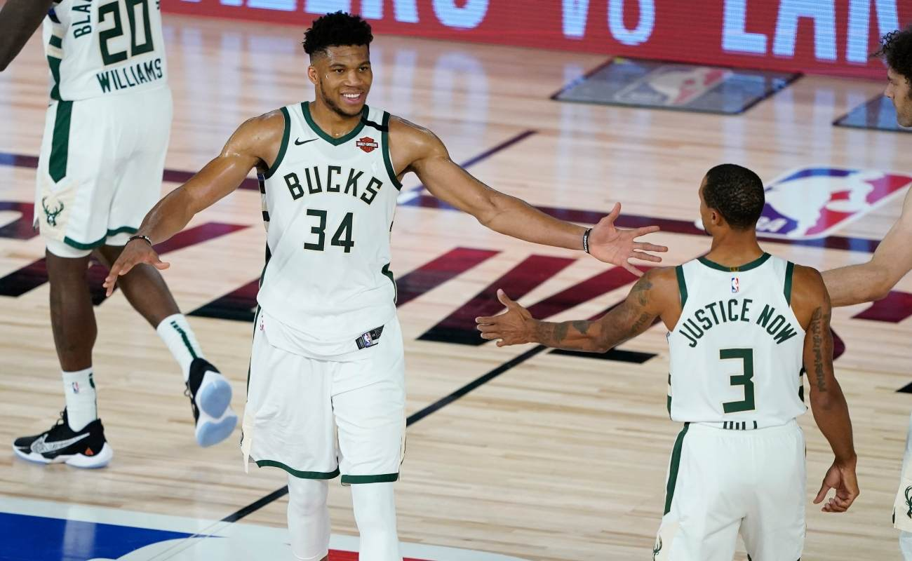 Giannis Antetokounmpo #34 of the Milwaukee Bucks celebrates with George Hill #3 and Robin Lopez #42 the team's win over the Orlando Magic in an NBA basketball first round playoff game on August 20, 2020 in Lake Buena Vista, Florida. (Photo by Ashley Landis - Pool/Getty Images)
