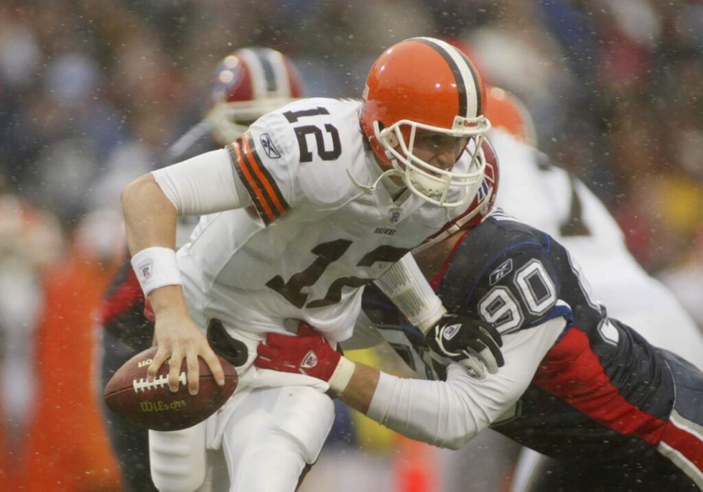 Quarterback Luke McCown #12 of the Cleveland Browns is sacked by defensive end Chris Kelsay #90 of the Buffalo Bills during the game on December 12, 2004 at Ralph Wilson Stadium in Orchard Park, New York. The Bills defeated the Browns 37-7. (Photo by Rick Stewart/Getty Images)