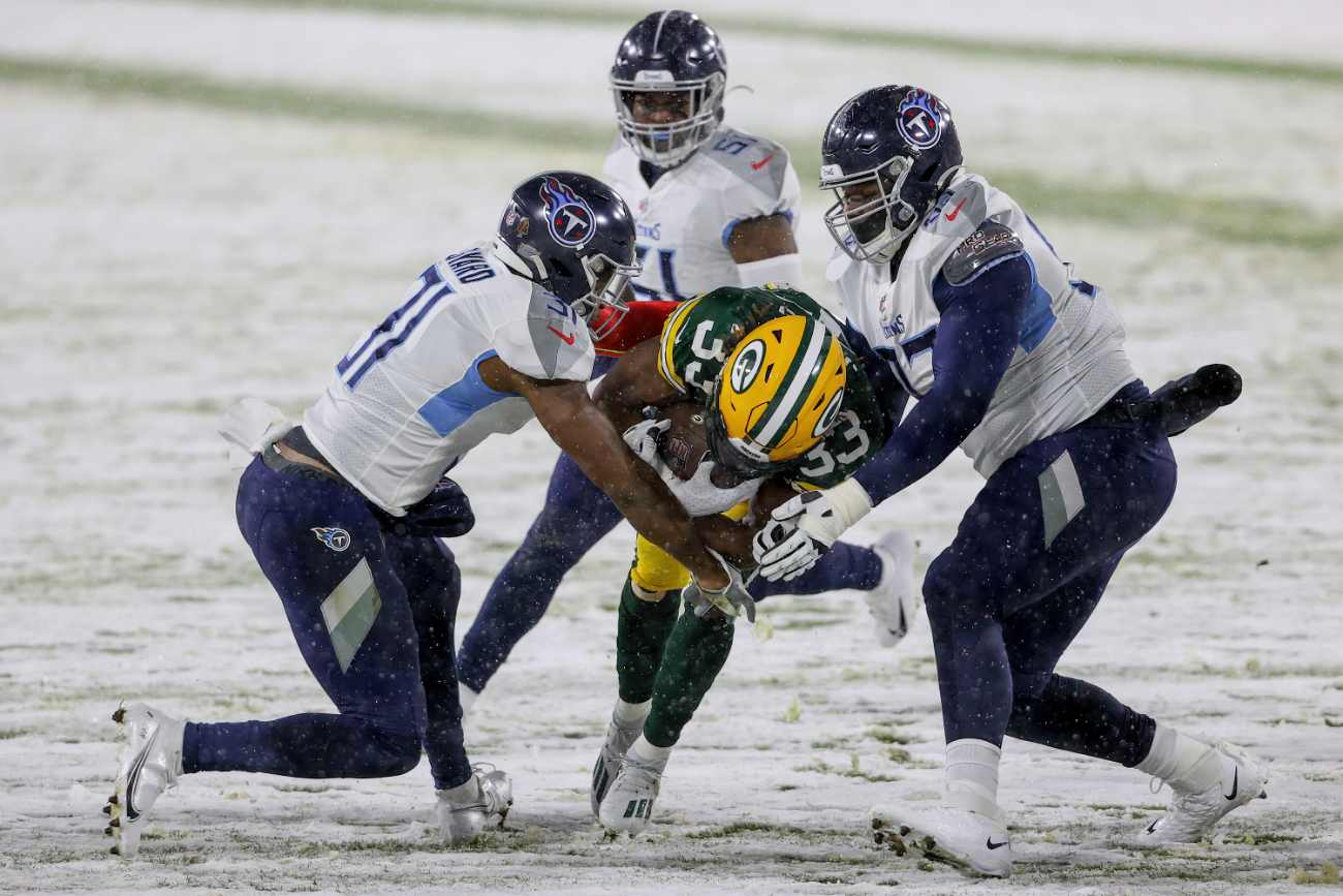 Aaron Jones #33 of the Green Bay Packers runs with the ball while being tackled by Kevin Byard #31 and Teair Tart #93 of the Tennessee Titans in the first quarter at Lambeau Field on December 27, 2020 in Green Bay, Wisconsin. (Photo by Dylan Buell/Getty Images)
