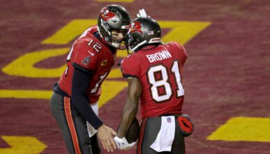 Quarterback Tom Brady #12 and wide receiver Antonio Brown #81 of the Tampa Bay Buccaneers celebrate after connecting for a first half touchdown pass against the Washington Football Team in the NFC Wild Card playoff game at FedExField on January 09, 2021 in Landover, Maryland. (Photo by Rob Carr/Getty Images)