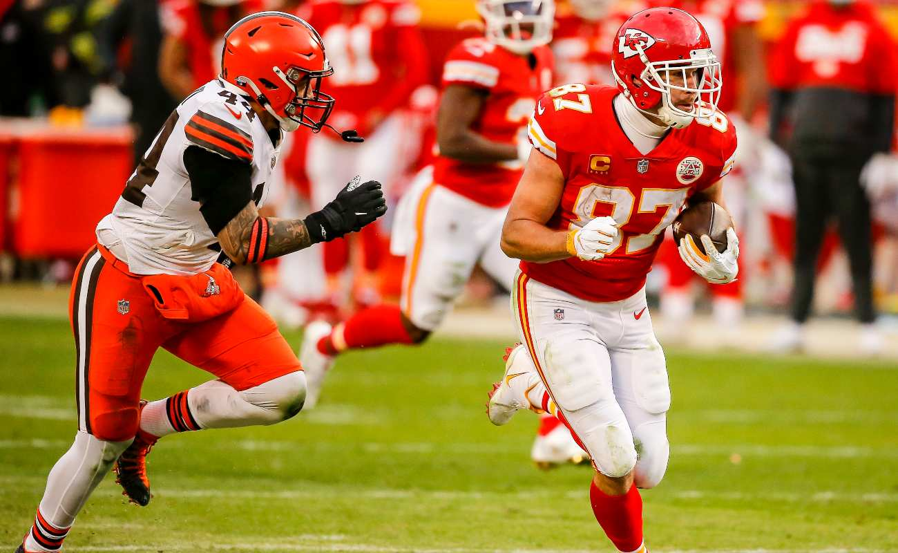 Travis Kelce #87 of the Kansas City Chiefs runs after a pass catch behind Sione Takitaki #44 of the Cleveland Browns in the fourth quarter of the AFC Divisional Playoff at Arrowhead Stadium on January 17, 2021 in Kansas City, Missouri. (Photo by David Eulitt/Getty Images)