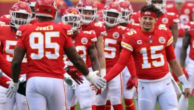 KANSAS CITY, MISSOURI - JANUARY 17: Quarterback Patrick Mahomes #15 of the Kansas City Chiefs welcomes defensive tackle Chris Jones #95 onto the field to start the AFC Divisional Playoff game against the Cleveland Browns at Arrowhead Stadium on January 17, 2021 in Kansas City, Missouri. (Photo by Jamie Squire/Getty Images)