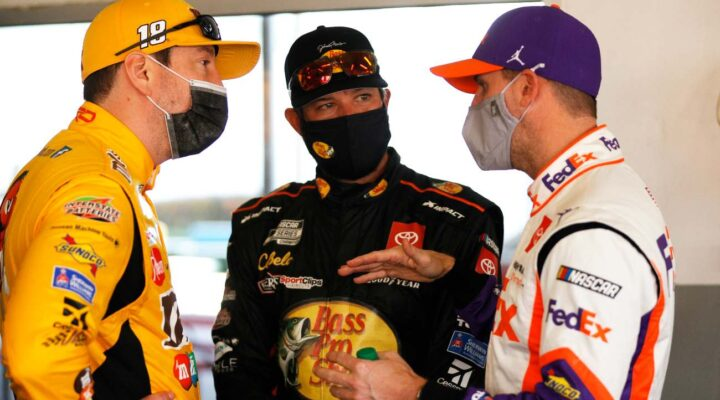 DAYTONA BEACH, FLORIDA - FEBRUARY 10: Kyle Busch, driver of the #18 M&M's Toyota, Martin Truex Jr., driver of the #19 Bass Pro Shops Toyota, and Denny Hamlin, driver of the #11 FedEx Toyota, talk in the garage area during practice for the NASCAR Cup Series 63rd Annual Daytona 500 at Daytona International Speedway on February 10, 2021 in Daytona Beach, Florida. (Photo by Chris Graythen/Getty Images)