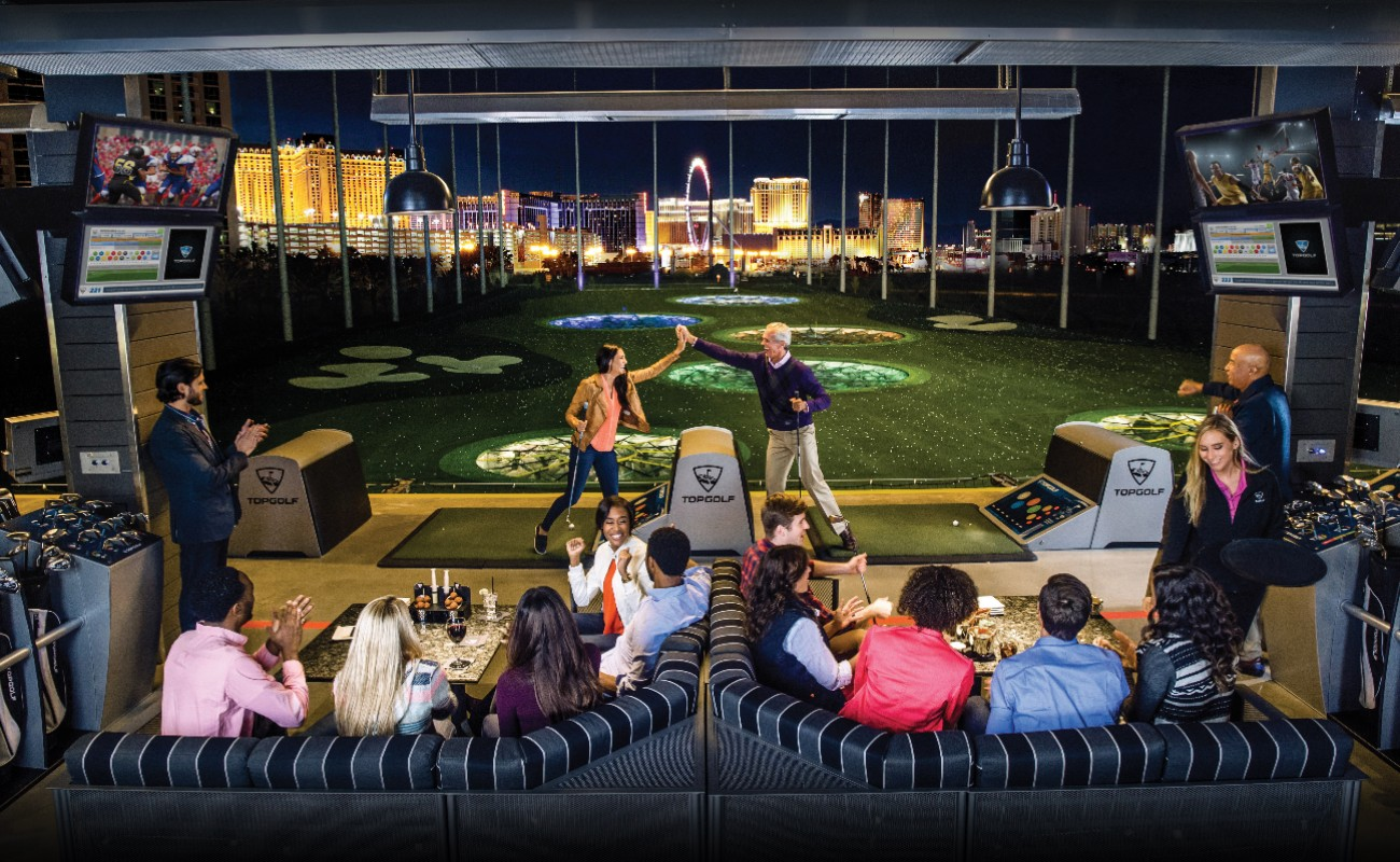 MGM Grand & Topgolf Las Vegas with people playing during the evening and the night view showing from the windows.