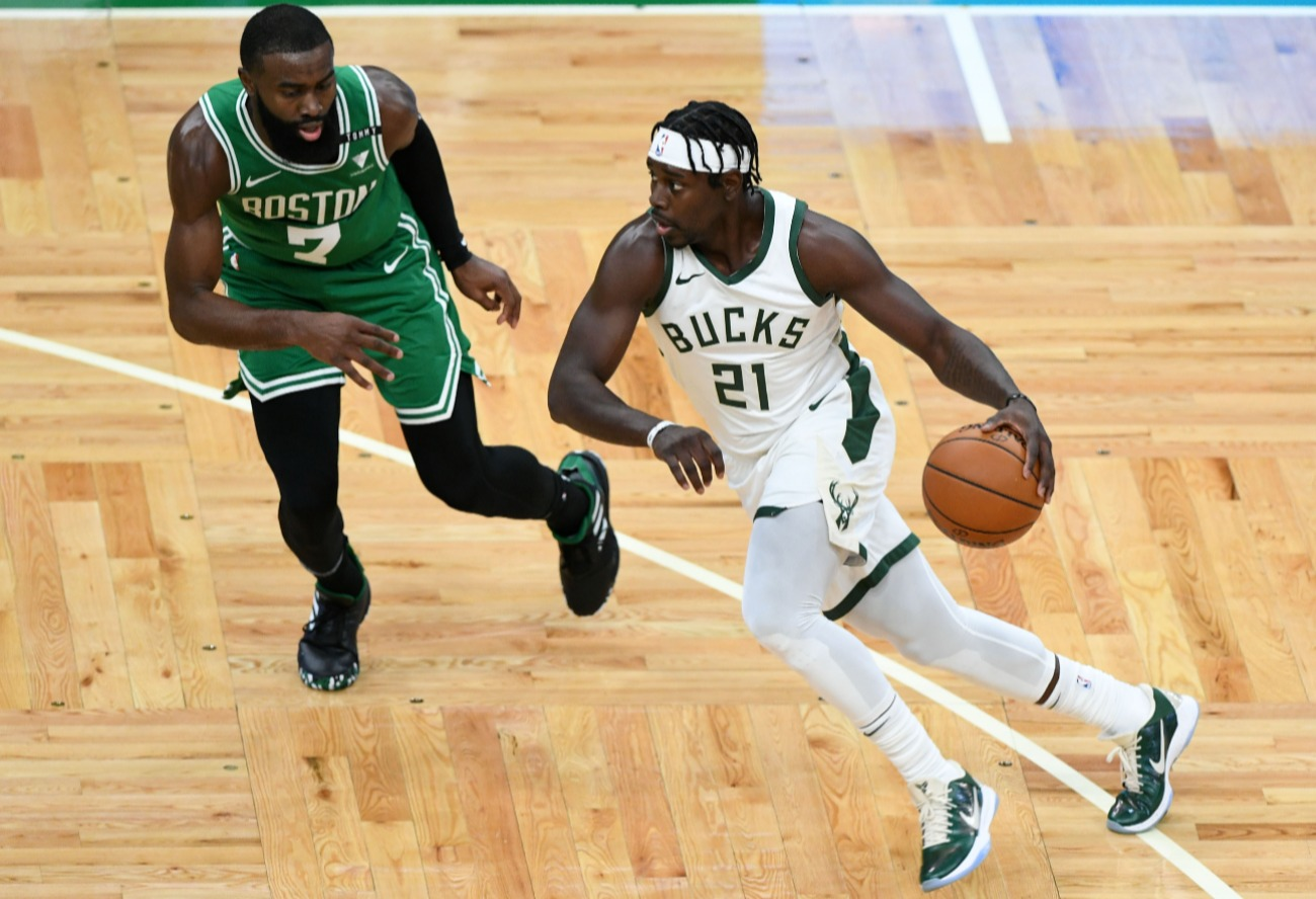 Jrue Holiday #21 of the Milwaukee Bucks dribbles the ball against Jaylen Brown #7 of the Boston Celtics during the first half at TD Garden on December 23, 2020 in Boston, Massachusetts.