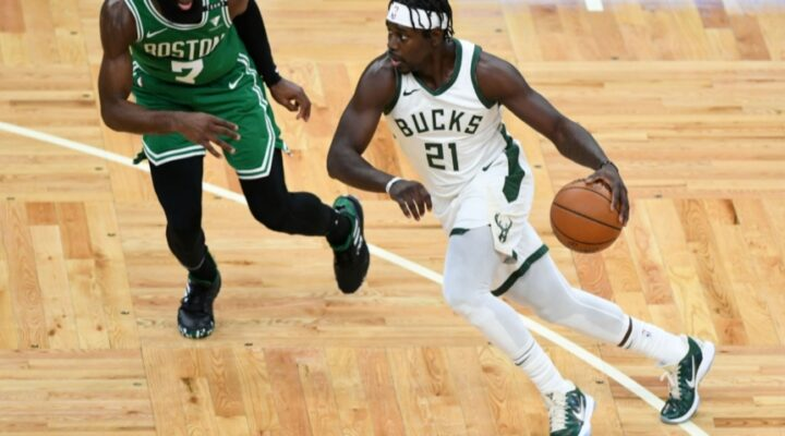 Jrue Holiday #21 of the Milwaukee Bucks dribbles the ball against Jaylen Brown #7 of the Boston Celtics during the first half at TD Garden on December 23, 2020 in Boston, Massachusetts.