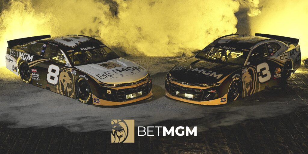 Two NASCAR racecars branded with BetMGM logos with golden lights and smoke in the background and the BetMGM logo on top