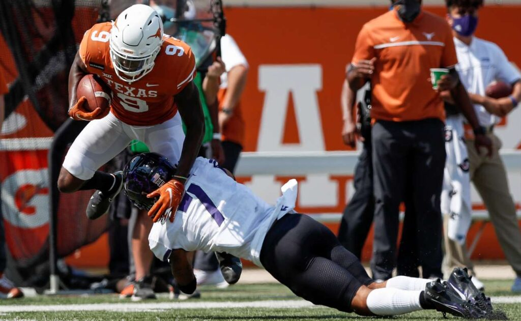 AUSTIN, TEXAS - OCTOBER 03: Al'Vonte Woodard #9 of the Texas Longhorns is tackled by Trevon Moehrig #7 of the TCU Horned Frogs in the third quarter at Darrell K Royal-Texas Memorial Stadium on October 03, 2020 in Austin, Texas. (Photo by Tim Warner/Getty Images)