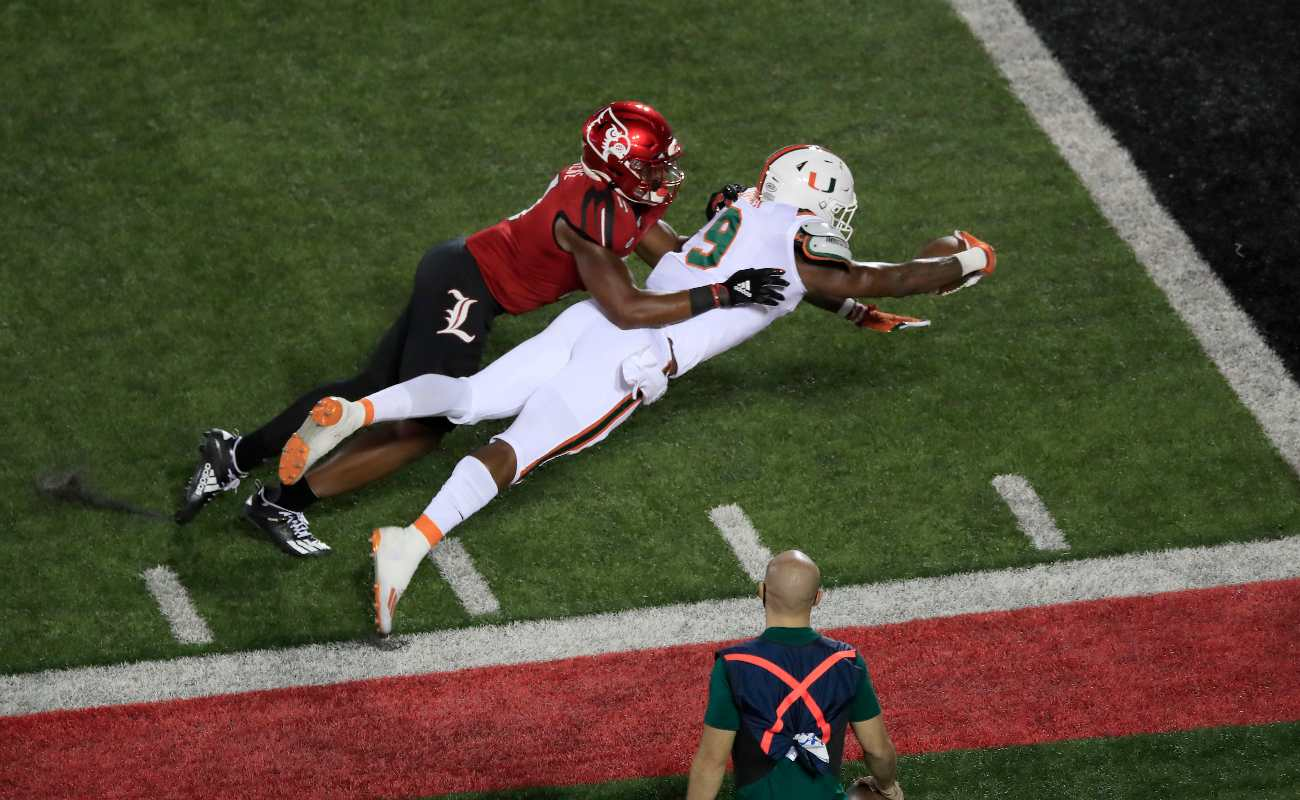 LOUISVILLE, KENTUCKY - SEPTEMBER 19: Brevin Jordan #9 of the Miami Hurricanes dives for the goal line against the Louisville Cardinals at Cardinal Stadium on September 19, 2020 in Louisville, Kentucky. (Photo by Andy Lyons/Getty Images)