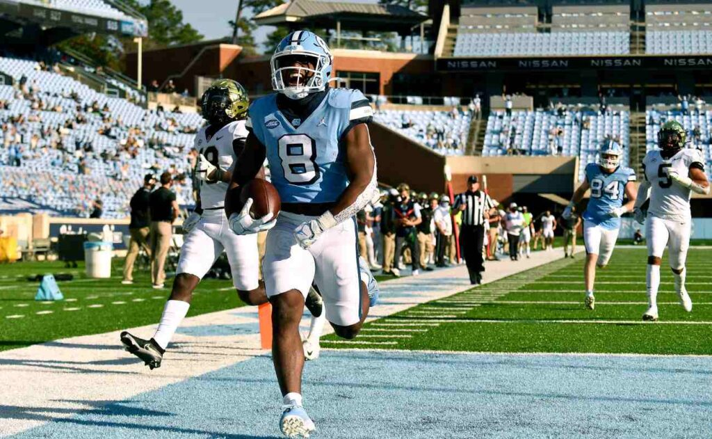 CHAPEL HILL, NORTH CAROLINA - NOVEMBER 14: Michael Carter #8 of the North Carolina Tar Heels scores a touchdown against the Wake Forest Demon Deacons during the fourth quarter of their game at Kenan Stadium on November 14, 2020 in Chapel Hill, North Carolina. The Tar Heels won 59-53. (Photo by Grant Halverson/Getty Images)