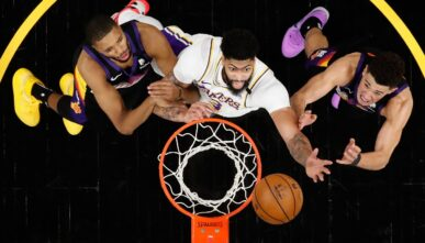 Anthony Davis #3 of the Los Angeles Lakers reaches for a rebound over Mikal Bridges #25 and Devin Booker #1 of the Phoenix Suns during the second half of Game One of the Western Conference first-round playoff series at Phoenix Suns Arena on May 23, 2021 in Phoenix, Arizona. The Suns defeated the Lakers 99-90. (Photo by Christian Petersen/Getty Images)