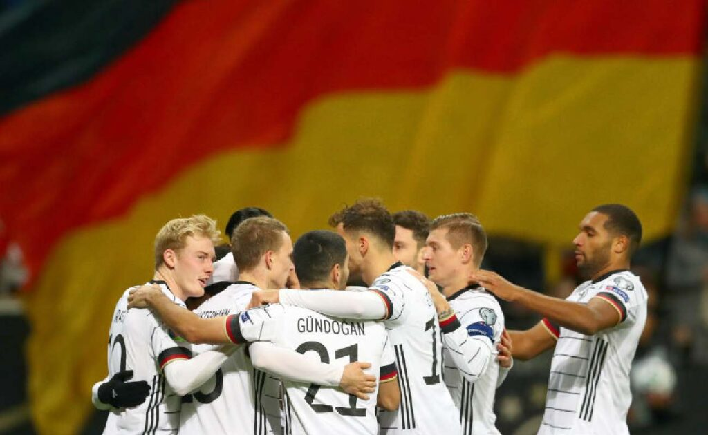 Alt: The German soccer team celebrate scoring a goal with the German flag in the background - Photo by Lars Baron/Bongarts/Getty Images