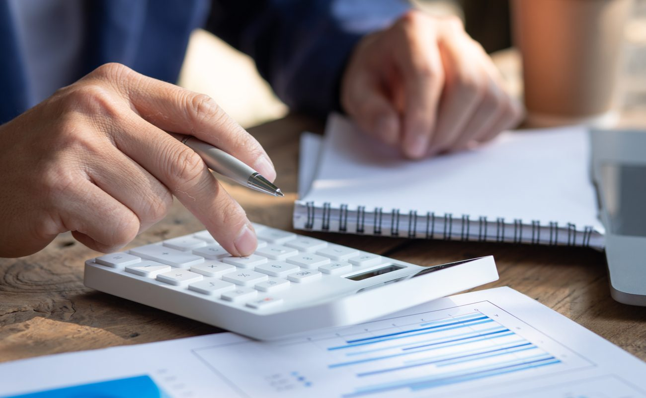 A man sits and calculates his expenses using a calculator and a notepad.