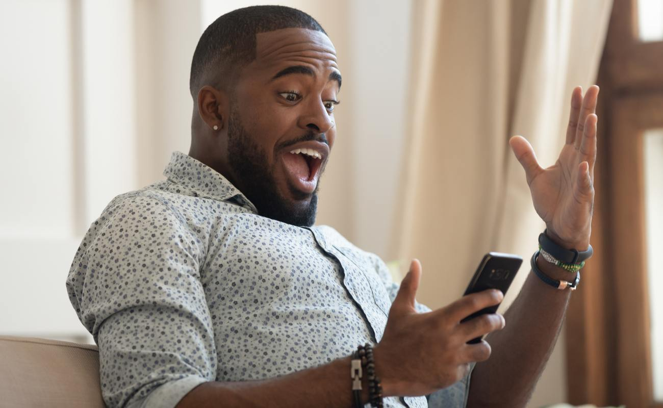 A man is surprised by his horse racing win on his phone.